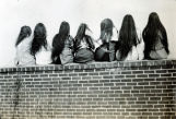Sitting on a Wall letting their hair dry